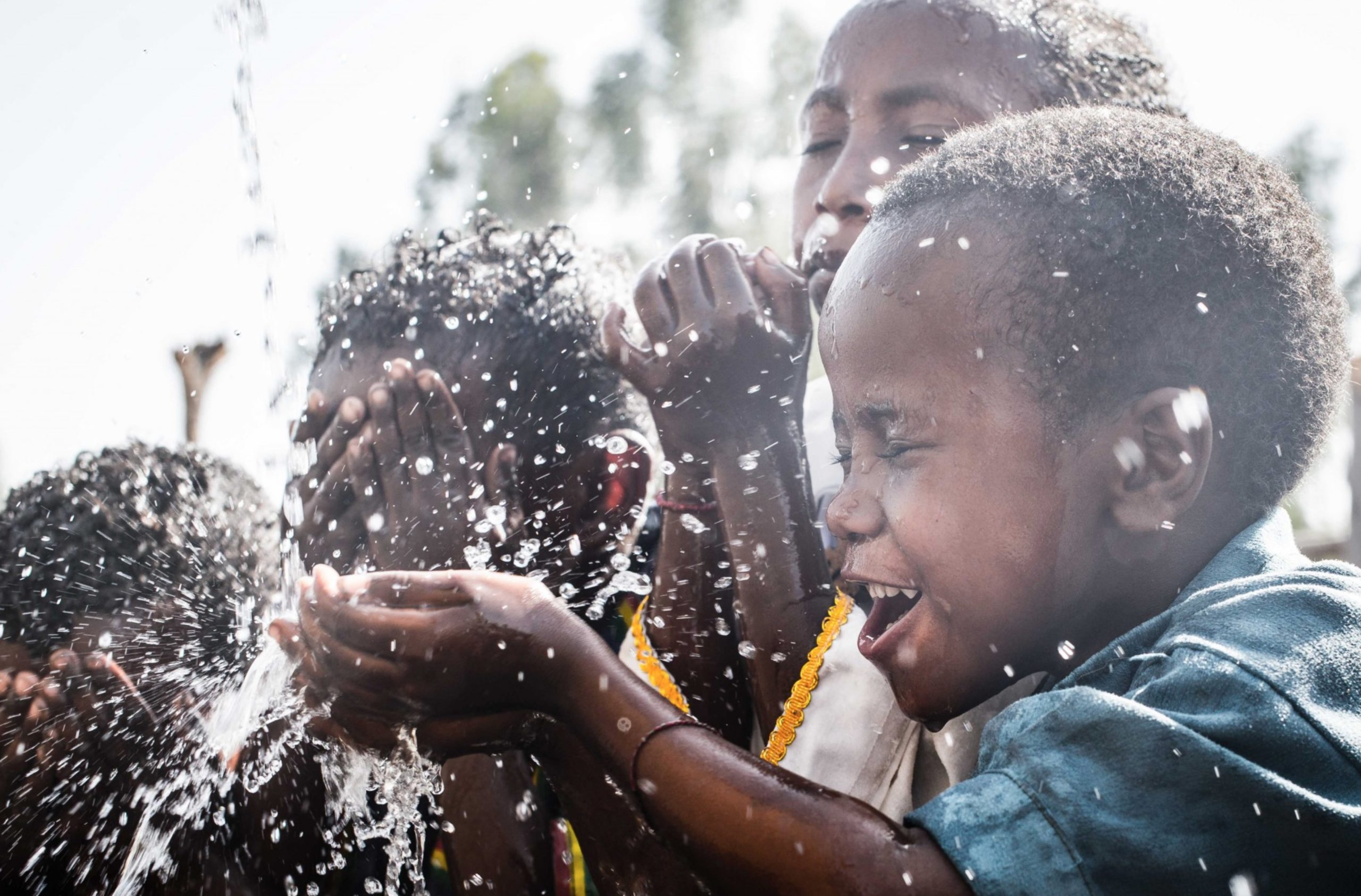 Kids in Tanzania getting clean drinking water which is donated by Bigger Picture Clothing in a partnership with Made Blue.