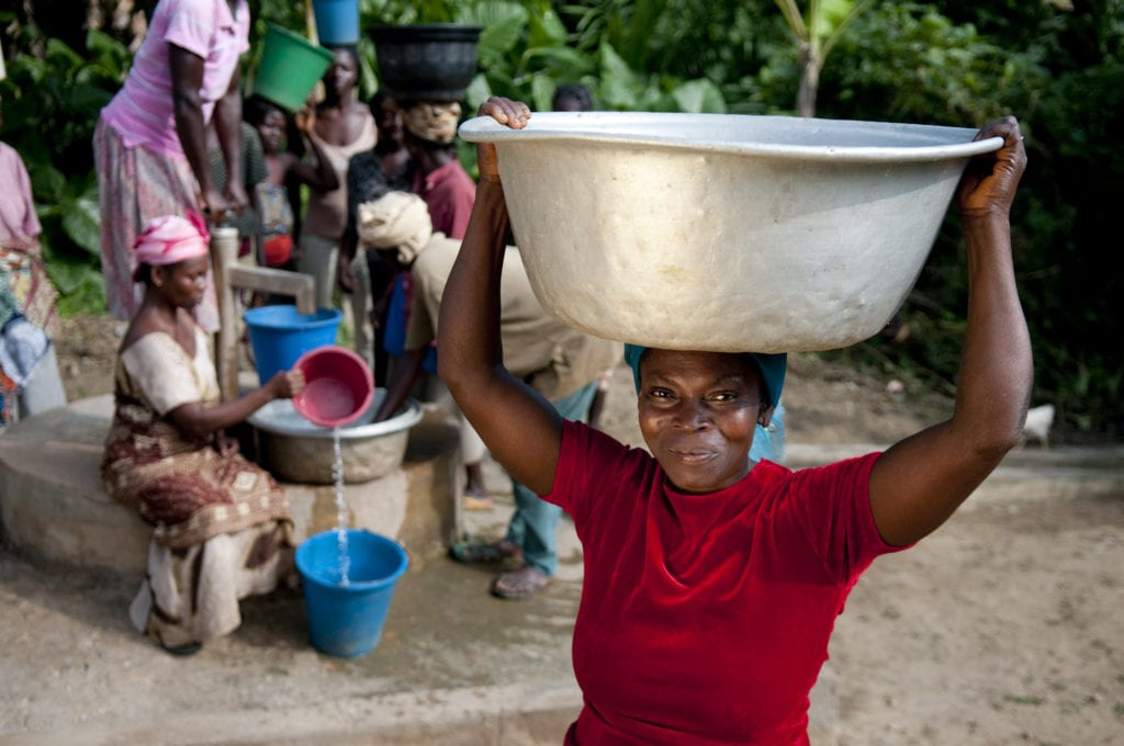 Woman holding bucket of clean drinking water