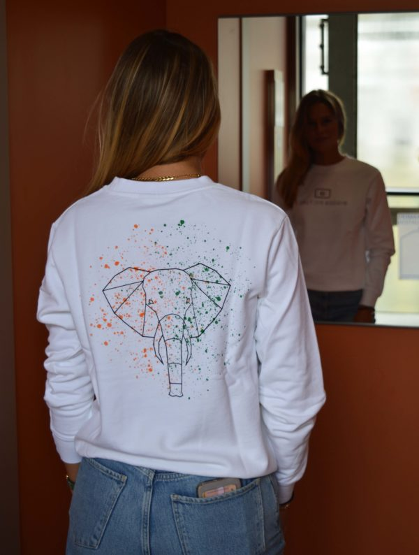 Pleun wearing our Energetic Elephant sweater, with the colorful back print of an elephant, which symbolizes the country of Ivory Coast that is supported for each product that we sell.