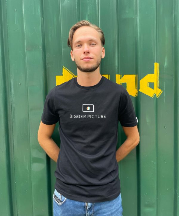Thijmen wearing bigger picture clothing black essential Tee, a T-shirt that is part of a sustainable fashion collection. The picture is made in Tilburg in The Netherlands near to the Lochal.