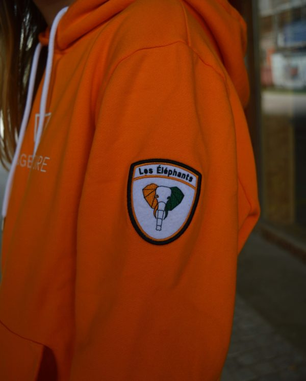 """The badge of our original orange hoodie, which communicates an elephant with """"les elephants"""" as text."""