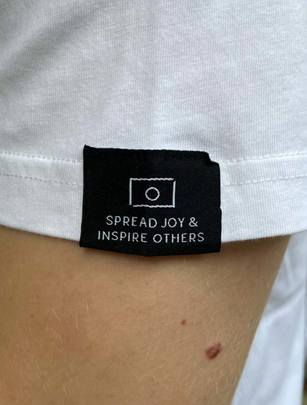 The sleevelabel of our white essential Tee that communicates one of our core values, namely 'spread joy & inspire others'.