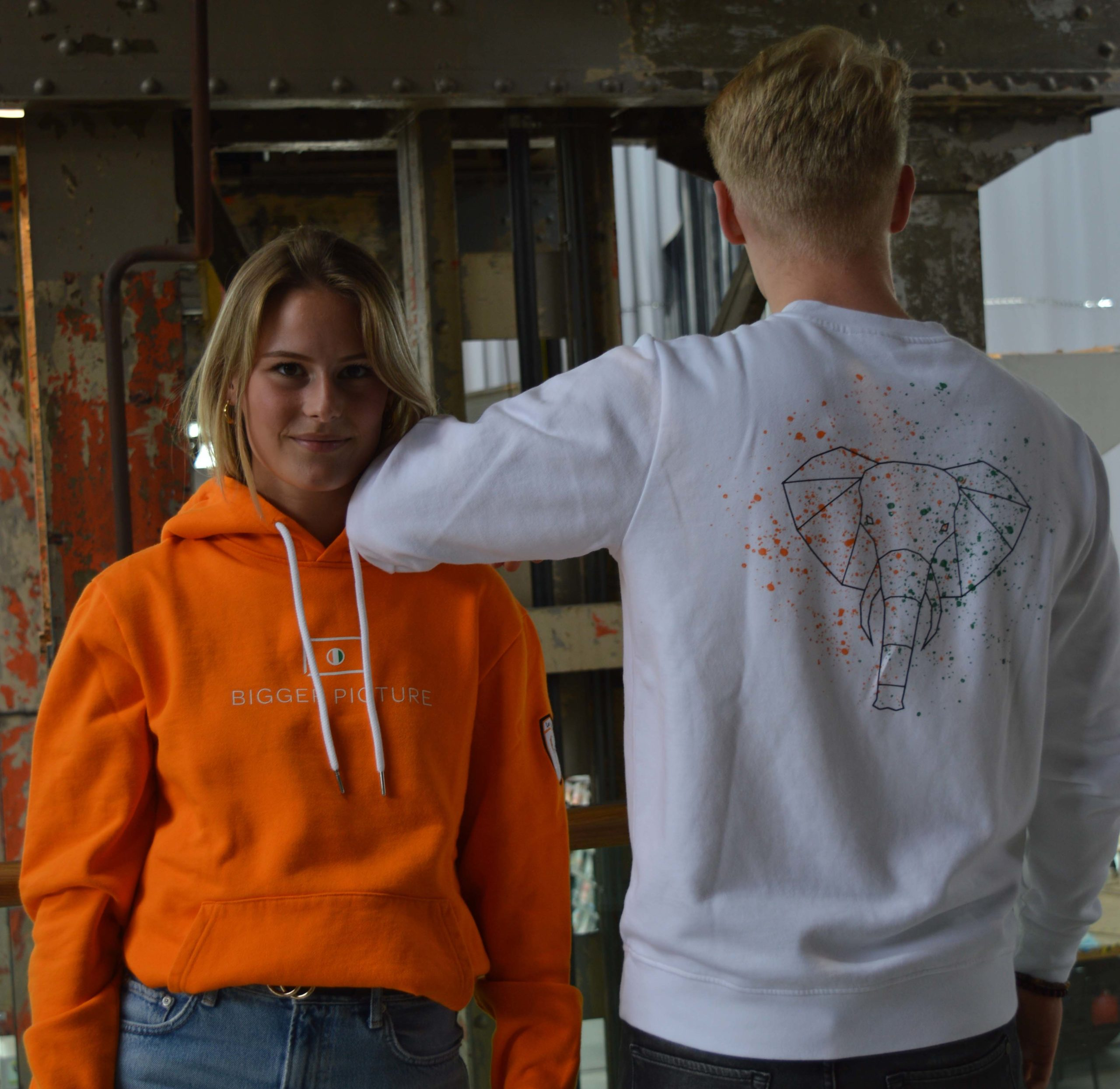 Pleun and Freek wearing the original orange hoodie and the energetic elephant sweater in the lochal in Tilburg, The Netherlands for the first photoshoot from slow-fashion brand Bigger Picture Clothing.