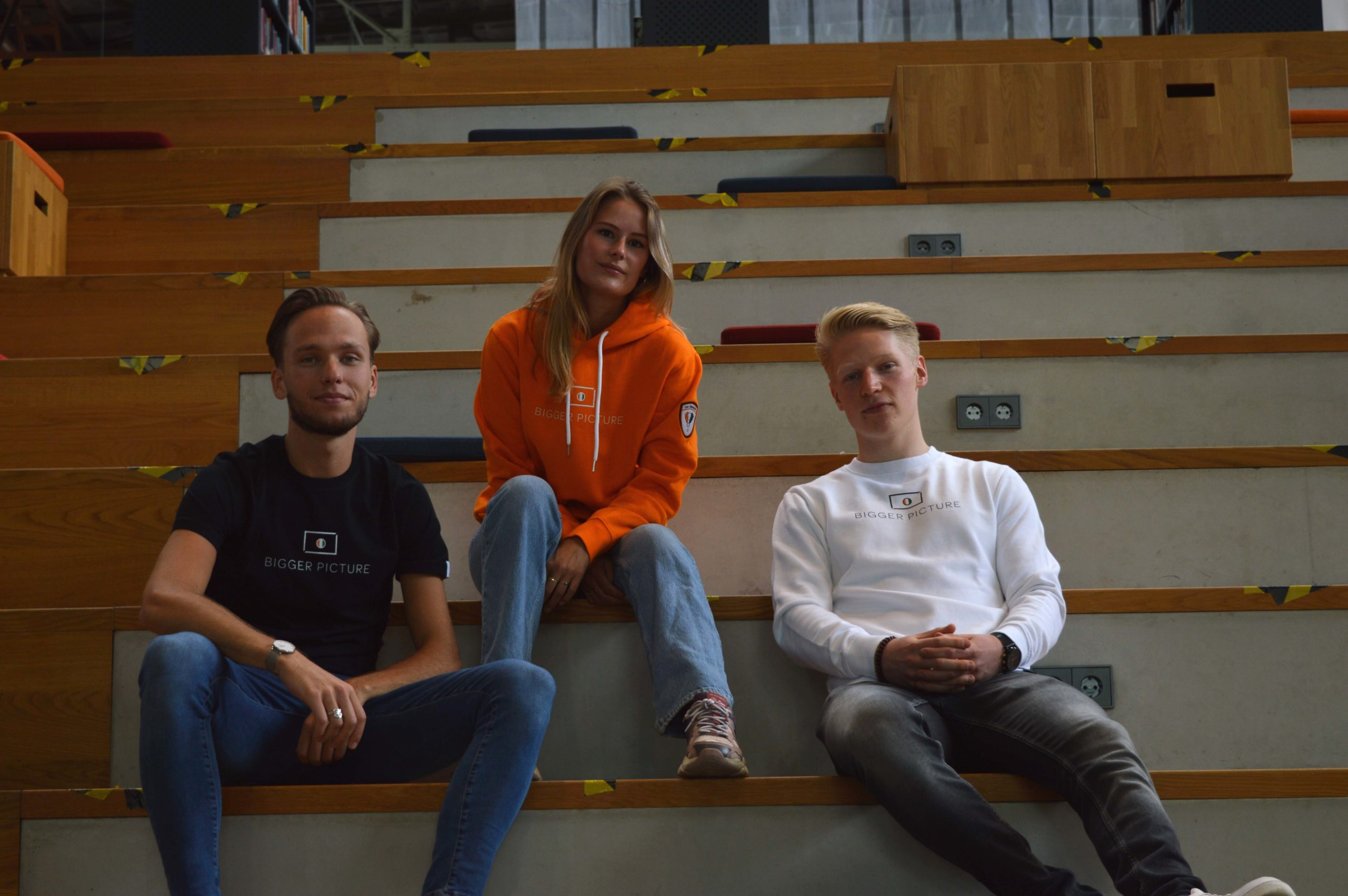 Freek, Pleun and Thijmen sitting on the stairs in the lochal in Tilburg for the first ever photoshoot of Dutch sustainable clothing brand Bigger Picture Clothing.